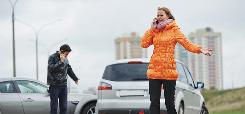 Agitated woman talking on the phone after a car accident on a cold, gray day.