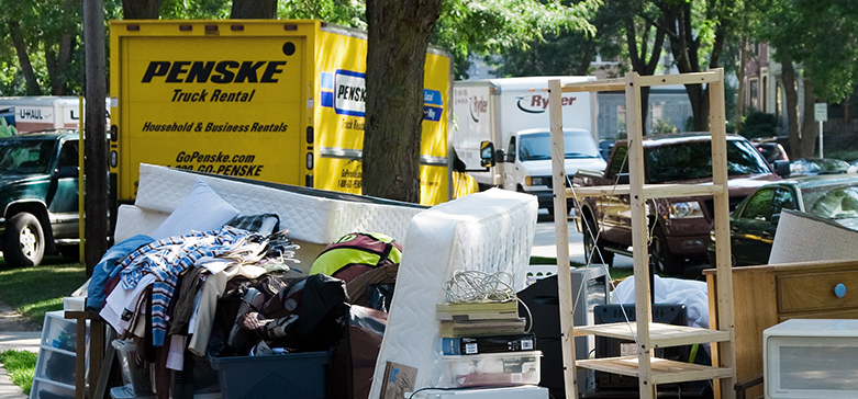 Moving Out photo by John Benson depicts a yard filled with disorganized piles of household items and moving trucks.