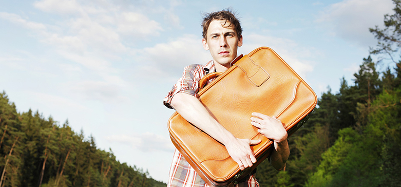 Young man in a field surrounded by trees, clutching a suitcase to his chest