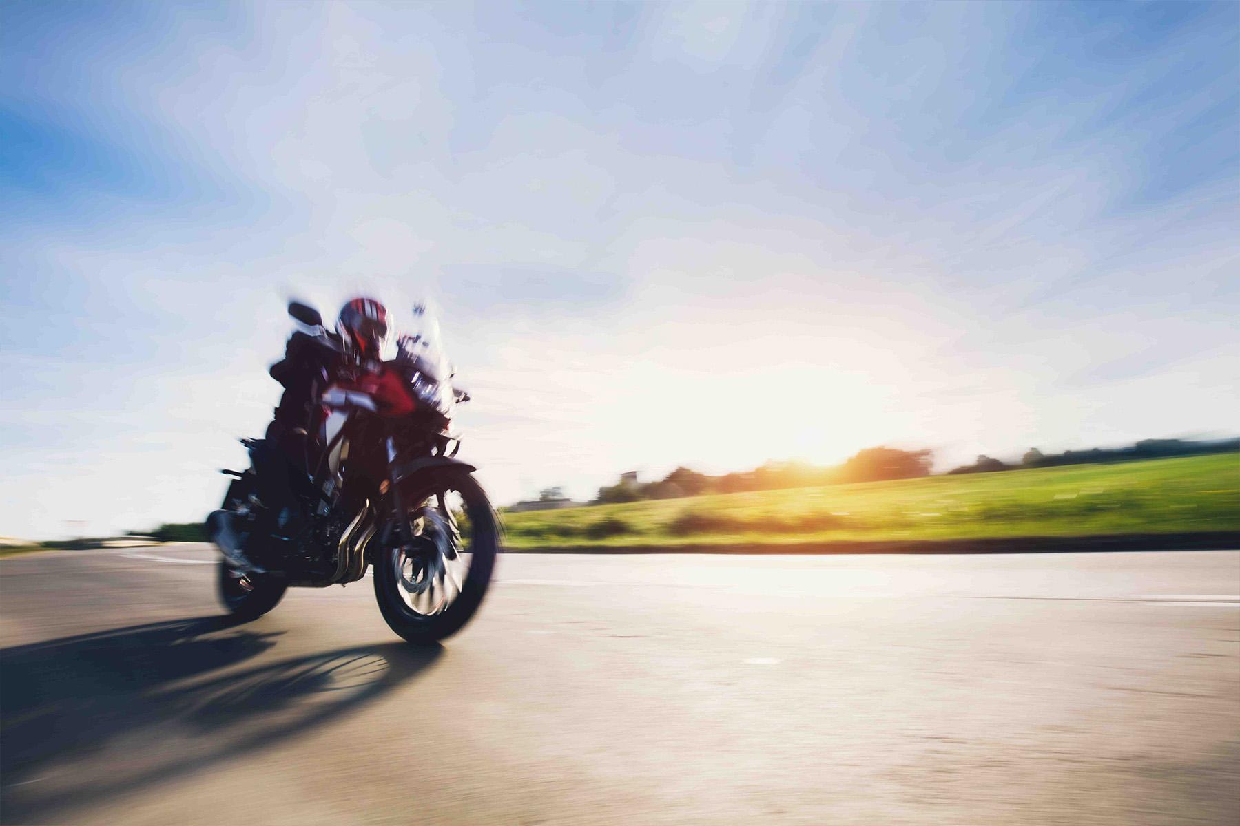 Motorcycle speeding down an open road.